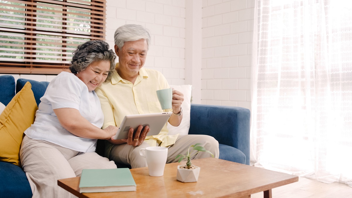 Asian Elderly Couple Using Tablet And Drinking Coffee In Living