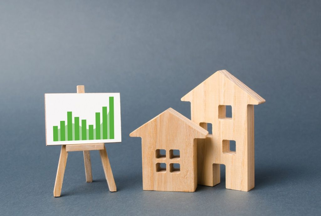 Wooden Figures Of Houses And A Poster With Information Charts With A Tendency Of Sales Growth. Increase Liquidity And Attractiveness Of Assets. Rent Or Cost Of Buying A Home. Real Estate Value Growth.