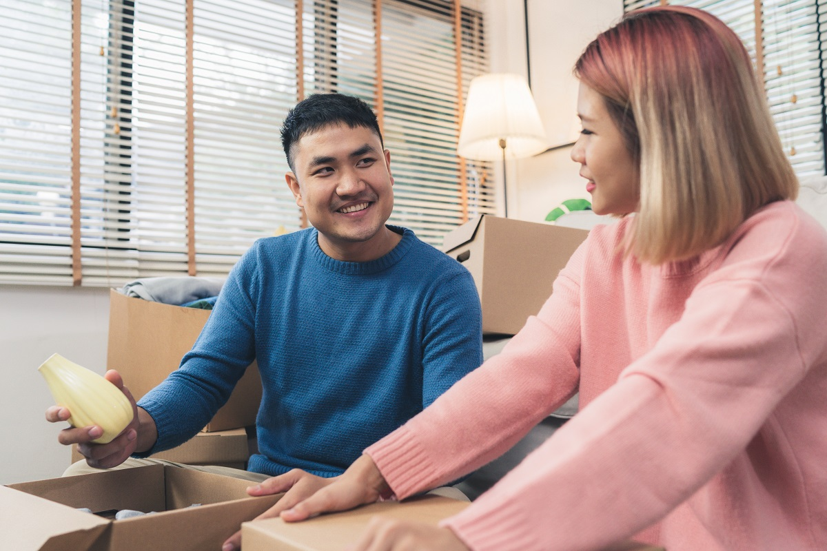 Young Happy Asian Couple Moving To Their New Home, Open Boxes To