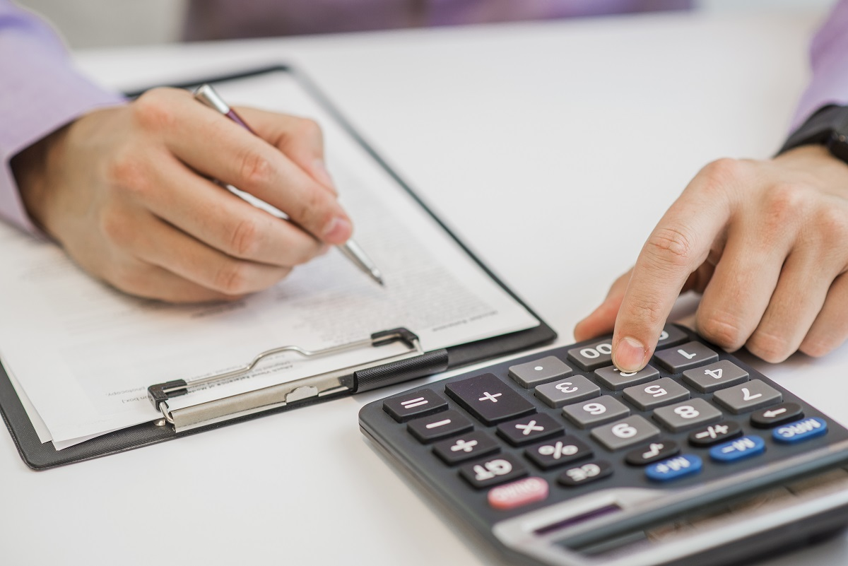 Close Up Of Businessman Calculating Invoices Using Calculator