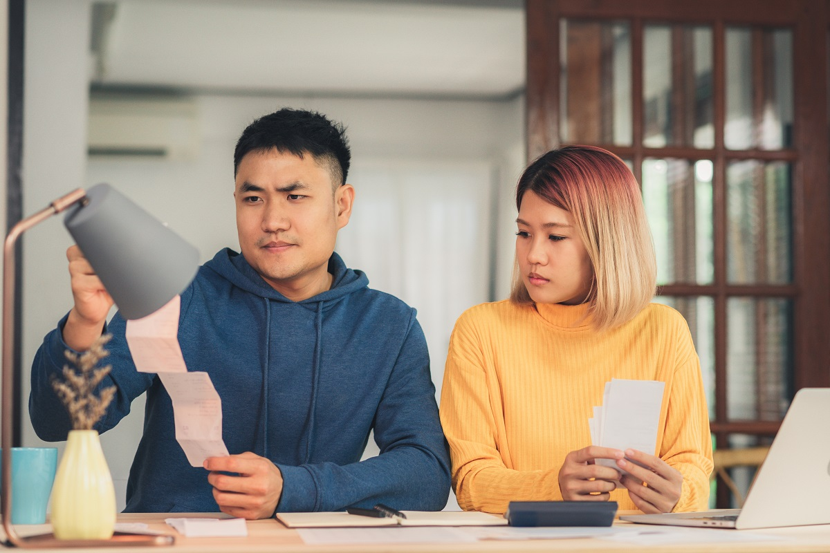 Young Stressed Asian Couple Managing Finances, Reviewing Their B