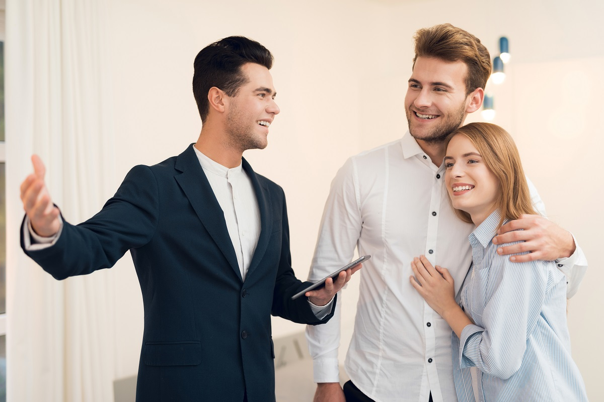Realtor In A Suit Shows A New Apartment To Clients.