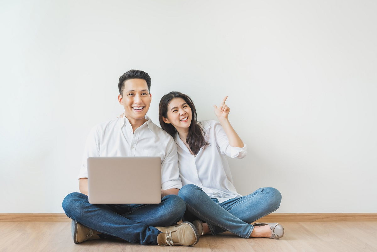 Asian Couple Sitting On Floor Using Laptop In White Room