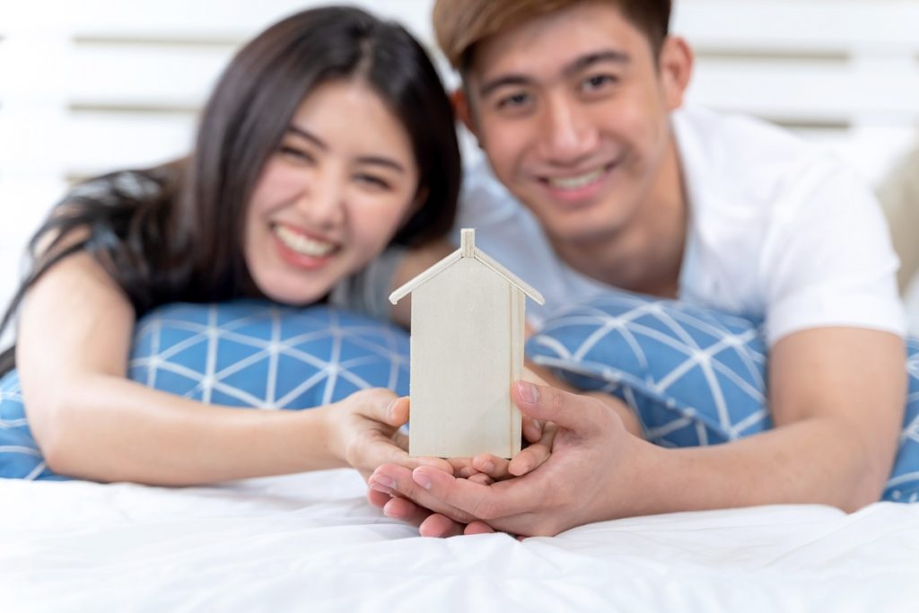 Young Couple Holding House Toy On The Bed