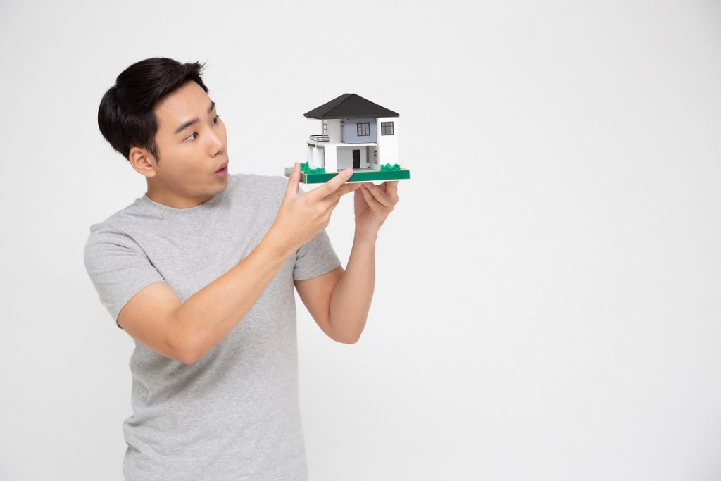 Happy Asian Man Holding Home Model, Planning To Take On A Large Loan For Purchase House Concept