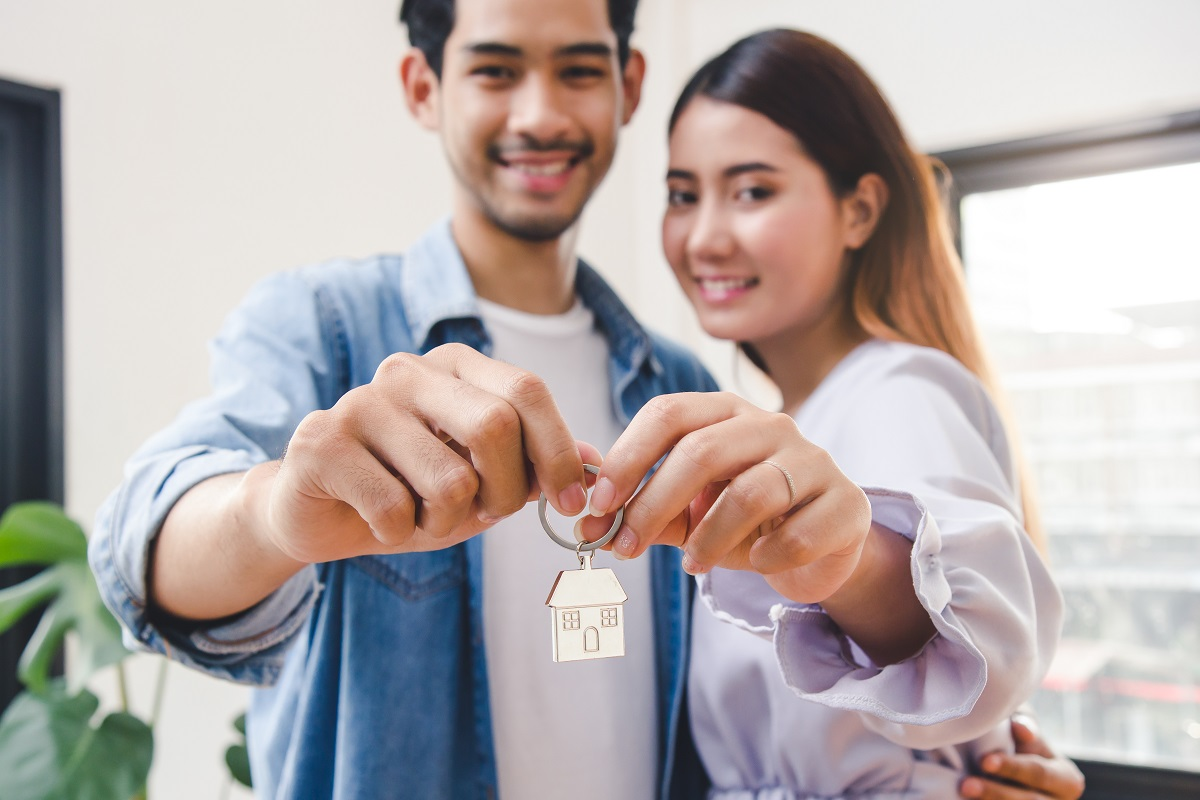 Relocation And Beginning New Life. Asian Couple Showing Keys Apa