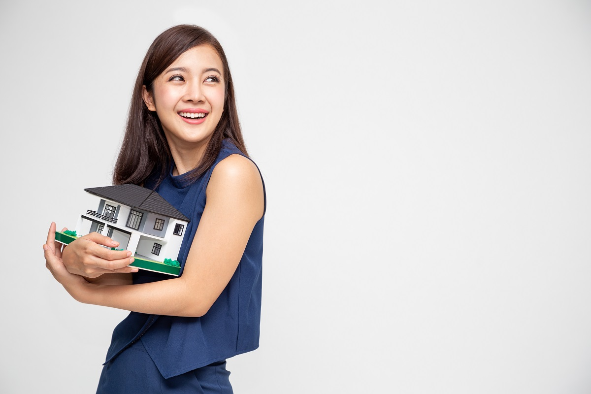 Young Asian Woman Smiling And Hugging Dream House Sample Model Isolated Over White Background, Real Estate And Home Insurance Concept