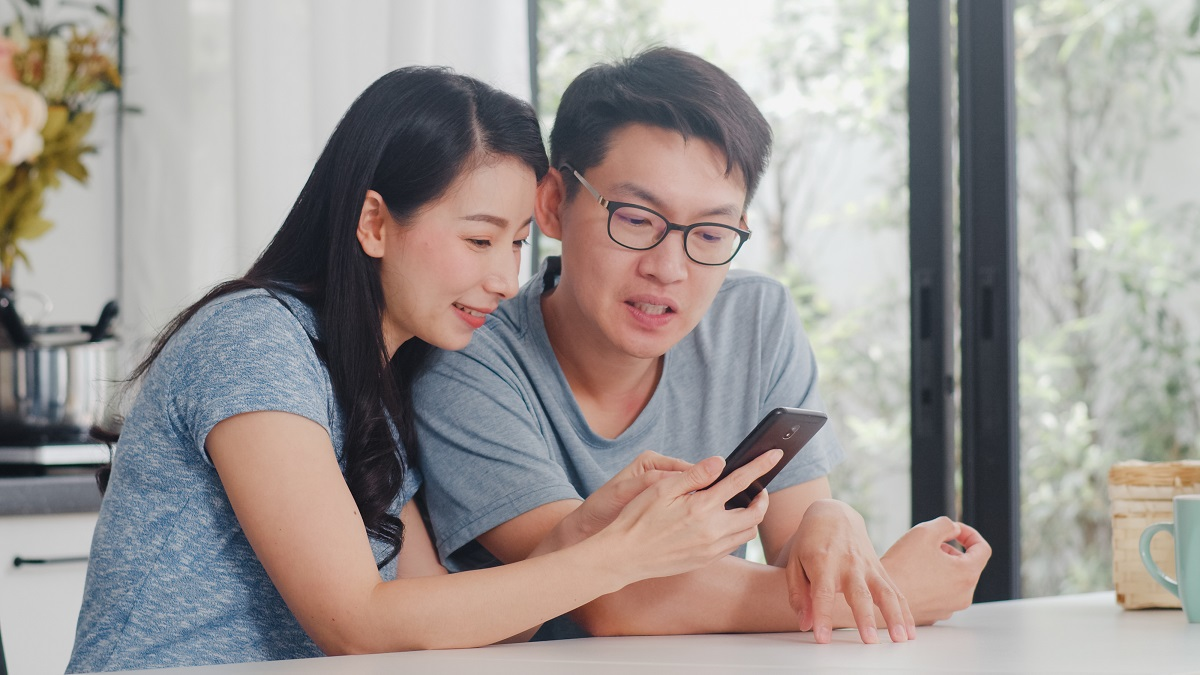Young Asian Couple Enjoy Shopping Online On Mobile Phone At Home