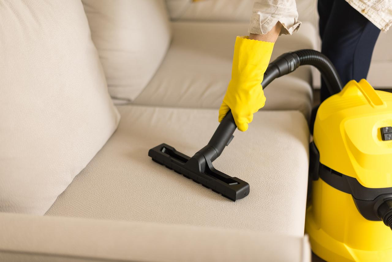 A woman vacuuming her living room sofa