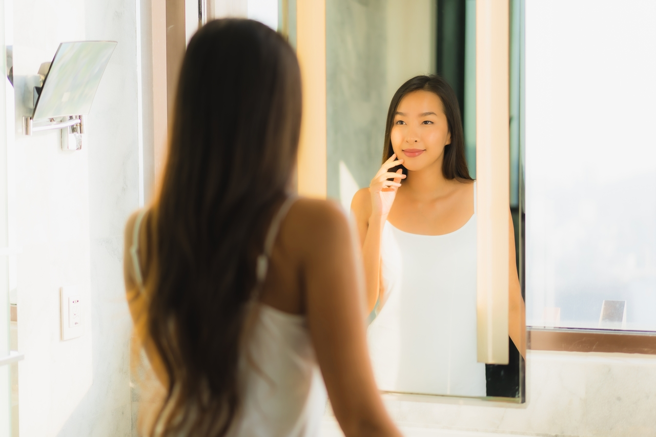 A woman doing her makeup in her bathroom