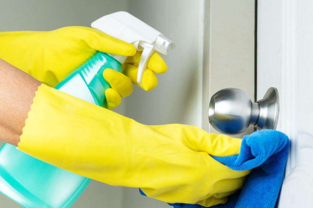 A person disinfecting a door knob