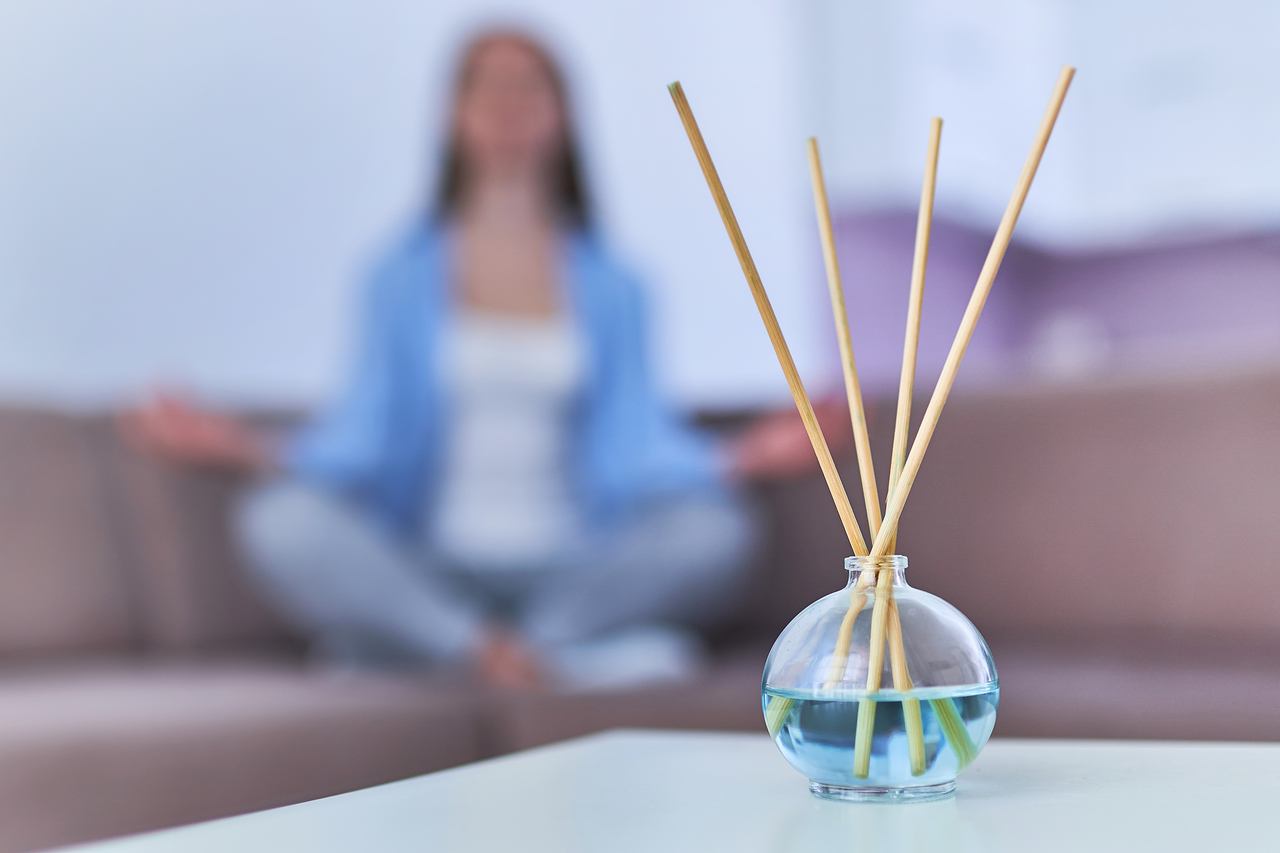 A woman doing yoga with aromatherapy sticks in the foreground