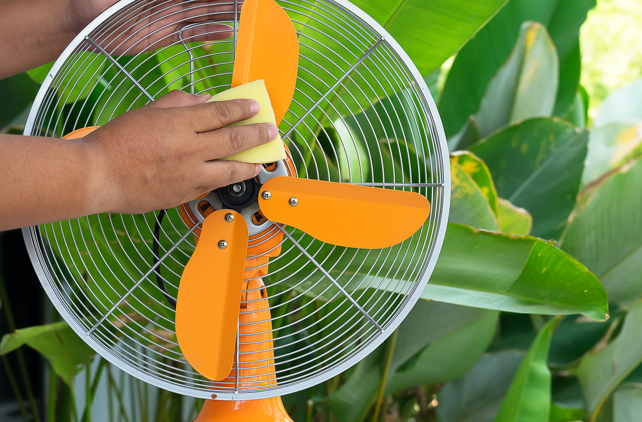 A hand cleaning an electric fan