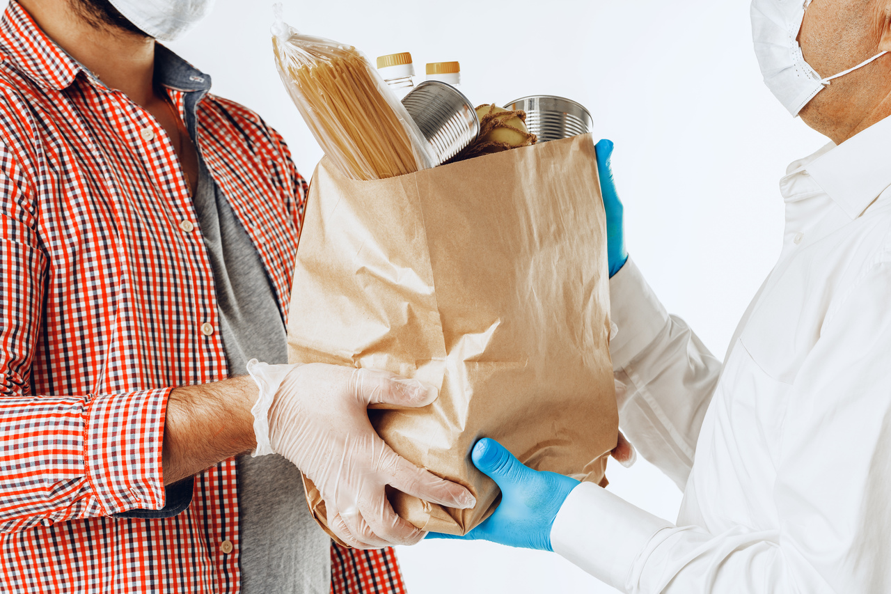 A delivery man and costumer exchanging groceries
